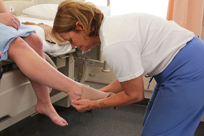 Nurse applying compression stocking to a patient.